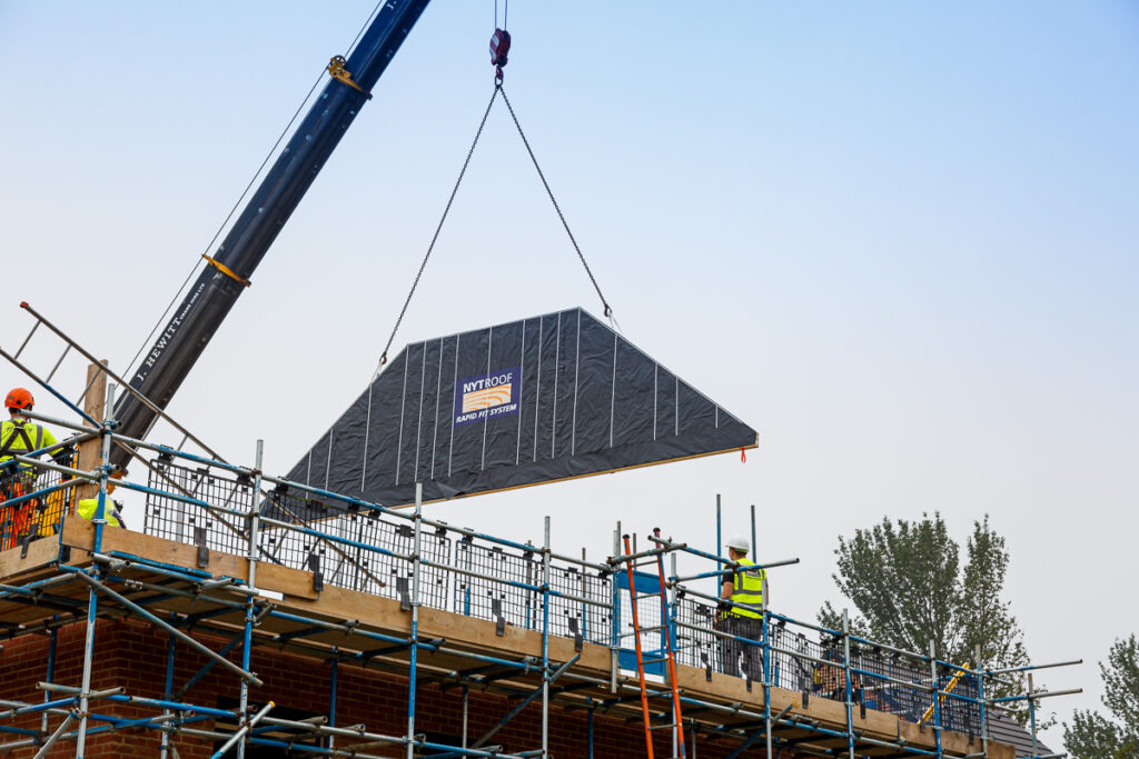 A spandrel panel being lowered into place ready to construct the NYTROOF, which is a panelised room in the roof system